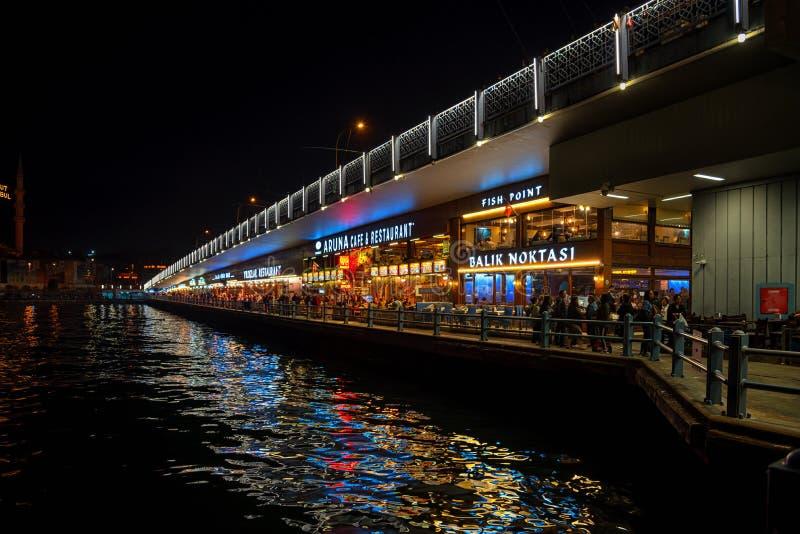 在加拉塔桥梁下的鱼餐馆在晚上,伊斯坦布尔土耳其 免版税库存图片
