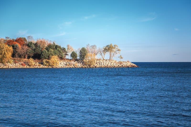 在加拿大人Ontario湖,与云彩,秋天在小海岛上的秋天树的明白蓝天环境美化在水中 免版税库存图片