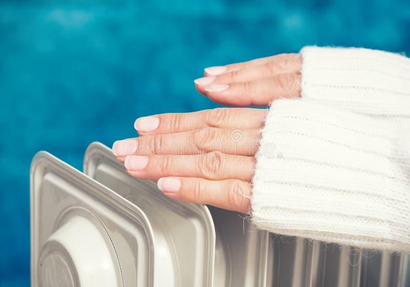 在加热器上的女性手 免版税库存图片