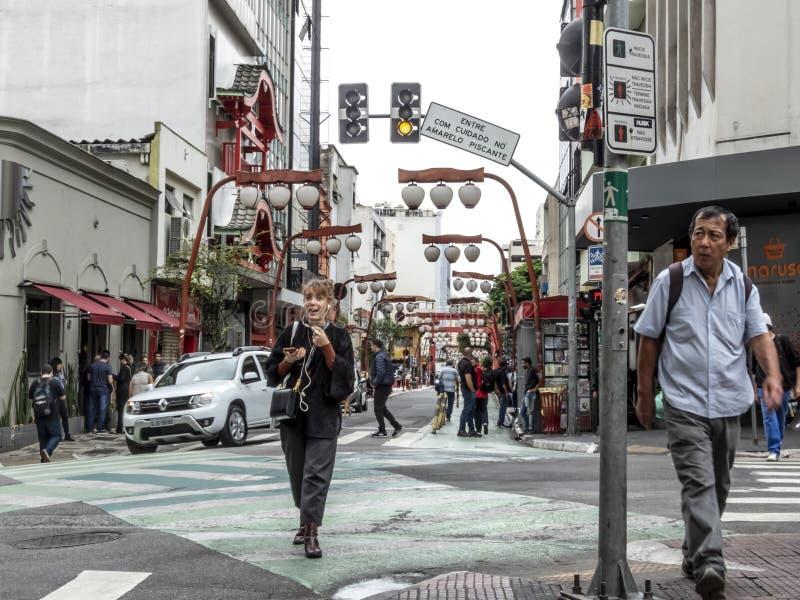 在加维奥布埃诺街道的步行者和车运动在利贝尔达迪区,圣保罗的中部有精选的焦点的 库存照片