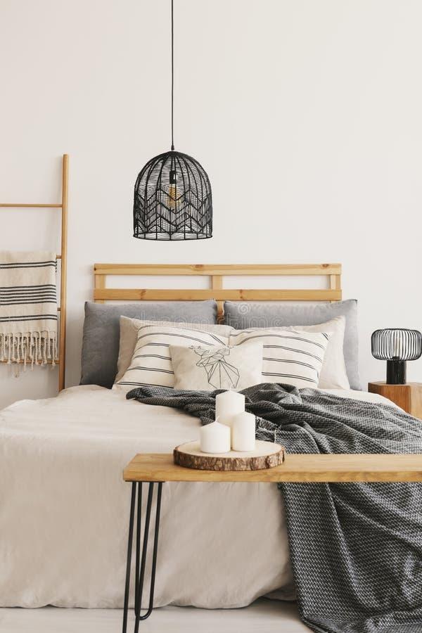 在加长型的床上的黑枝形吊灯与米黄鸭绒垫子、灰色毯子和枕头,与拷贝空间的真正的照片在空 库存图片