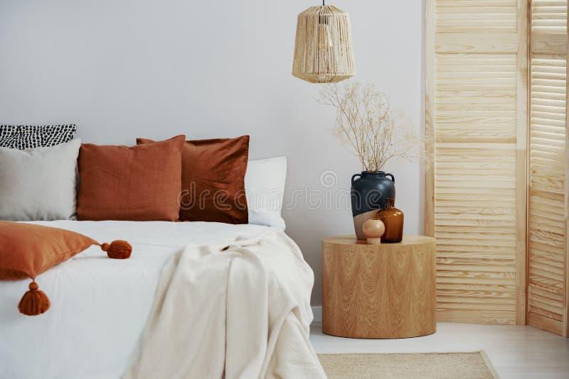 在加长型的床,在空的墙壁上的拷贝空间上的深黄和灰色枕头 图库摄影