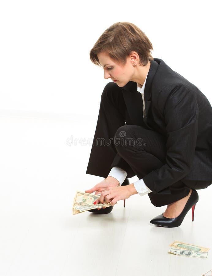 在劫掠现金的地板上的女商人 免版税库存图片