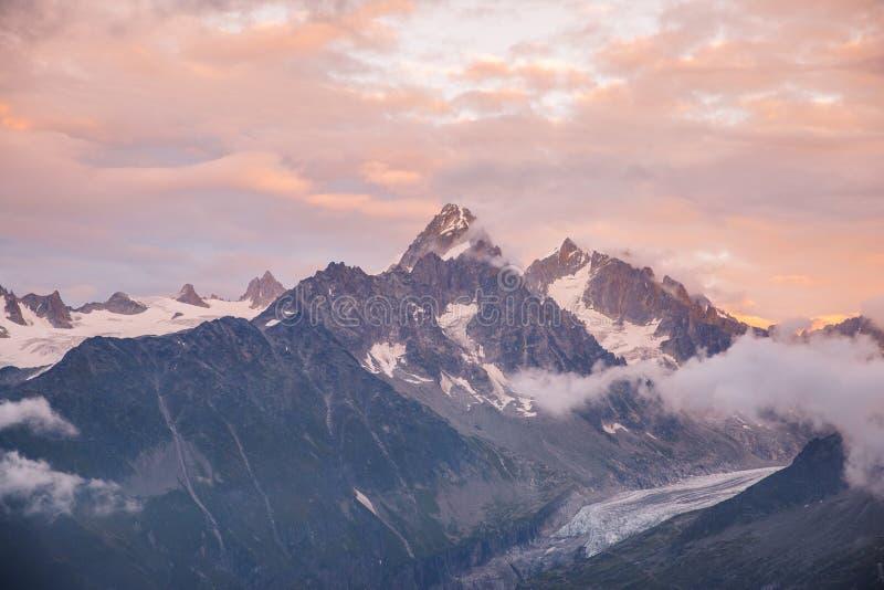 在勃朗峰山脉和冰川的多云日落 免版税库存图片
