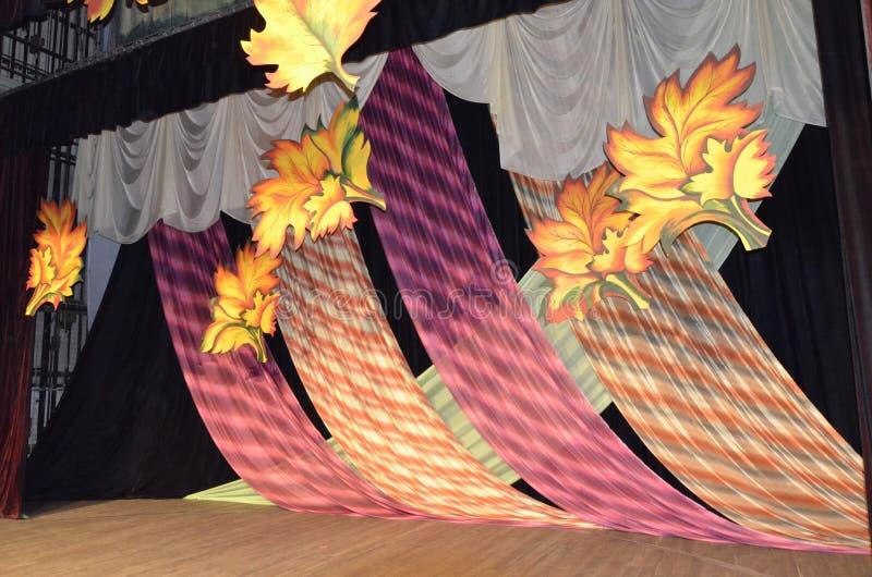 在包括伯根地布料的阶段的装饰装饰用黄色叶子 库存图片