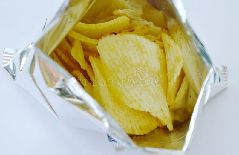 在包装在白色背景的铝芯的土豆片 免版税库存照片