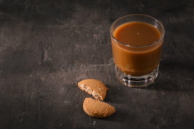 在包装纸和杯的被分类的曲奇饼咖啡用在黑暗的背景的牛奶 免版税库存照片