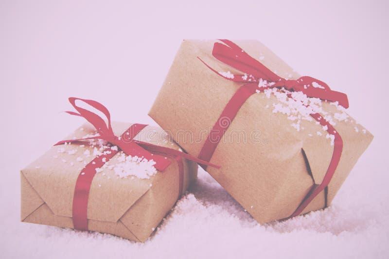 在包装纸的圣诞节礼物与减速火箭红色丝带的葡萄酒 库存照片