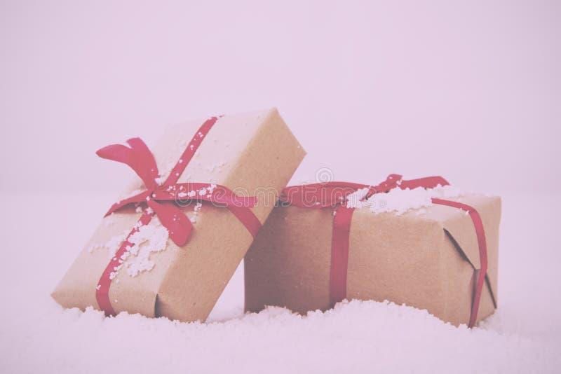 在包装纸的圣诞节礼物与减速火箭红色丝带的葡萄酒 库存图片