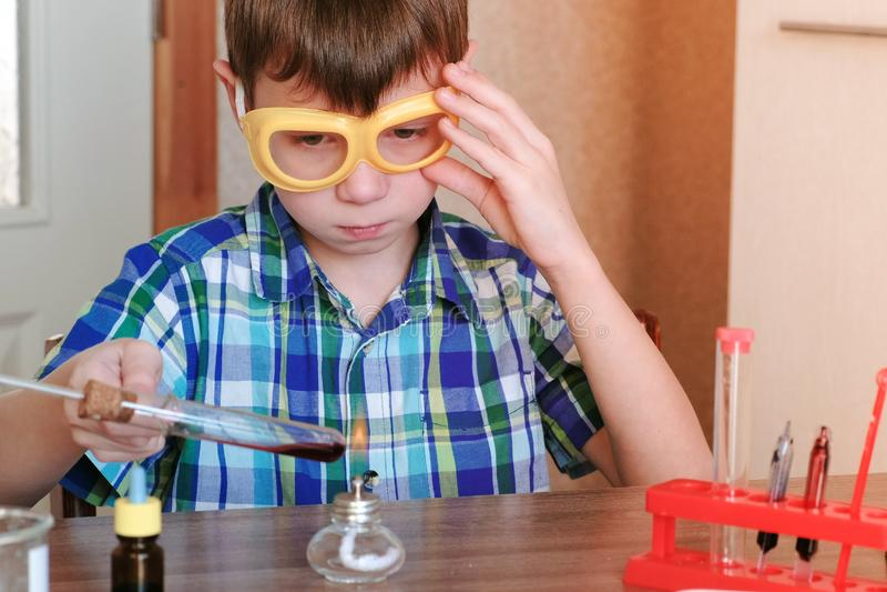 在化学的实验在家 男孩加热有红色液体的试管在灼烧的酒精灯 液体煮沸 库存图片