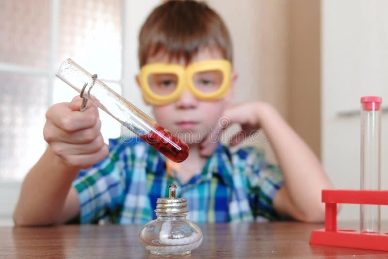 在化学的实验在家 男孩加热有红色液体的试管在灼烧的酒精灯 蓝蓝 库存图片