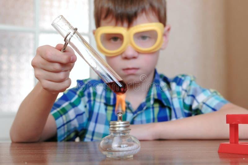 在化学的实验在家 男孩加热有红色液体的试管在灼烧的酒精灯 库存照片