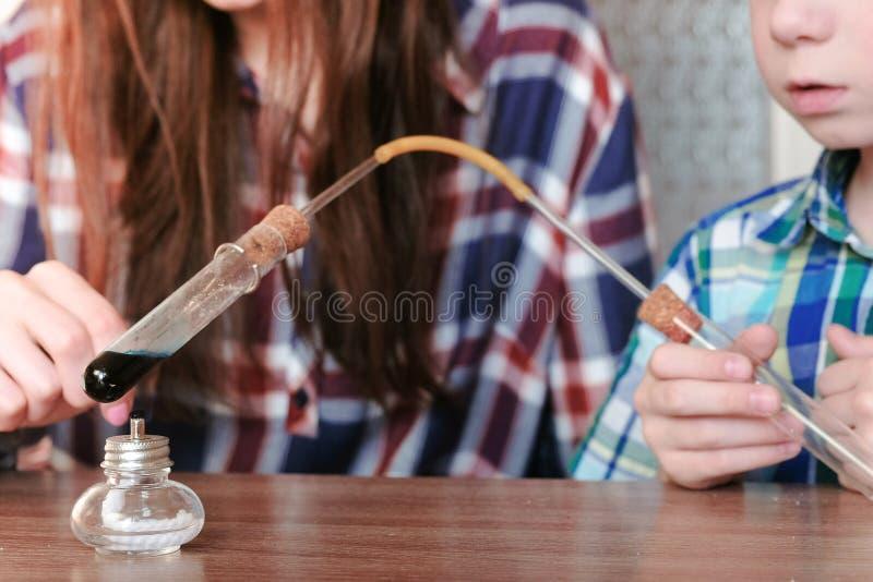 在化学的实验在家 男孩和他的妈妈加热有蓝色液体的试管在灼烧的酒精灯 免版税图库摄影