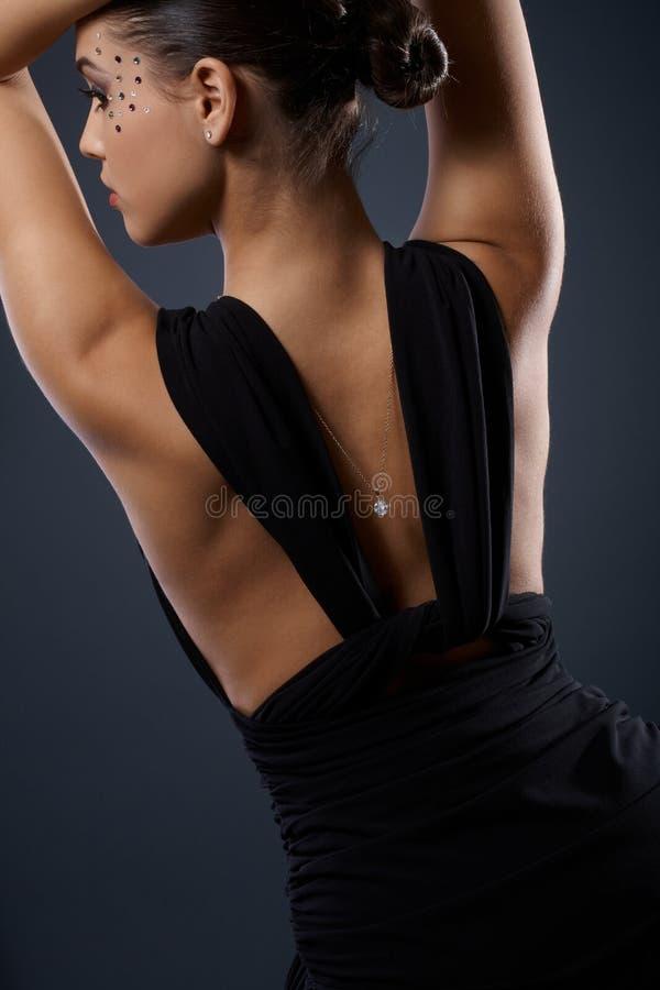 在化装舞会所穿着的服装的有吸引力的女性返回 库存照片