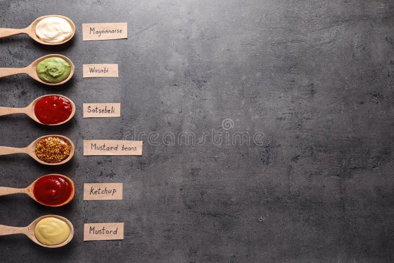 在匙子的不同的在灰色背景,平的位置的调味汁和名牌 库存图片