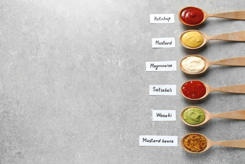 在匙子的不同的在灰色背景,平的位置的调味汁和名牌 免版税库存图片