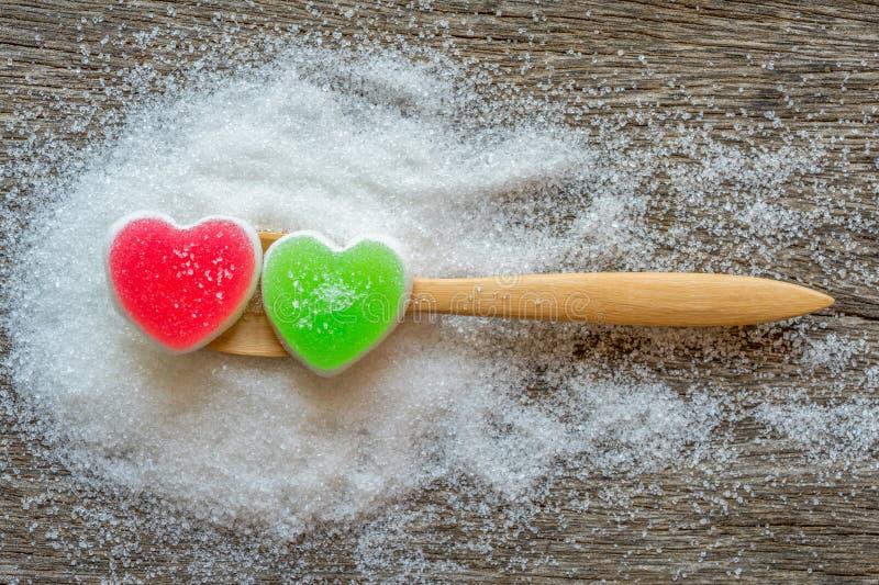 结冻在匙子的甜心形状在糖背景 免版税库存图片