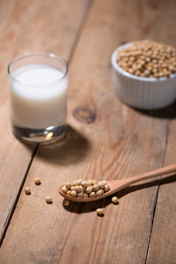 在匙子的豆奶或大豆牛奶和大豆豆在木桌上 库存图片