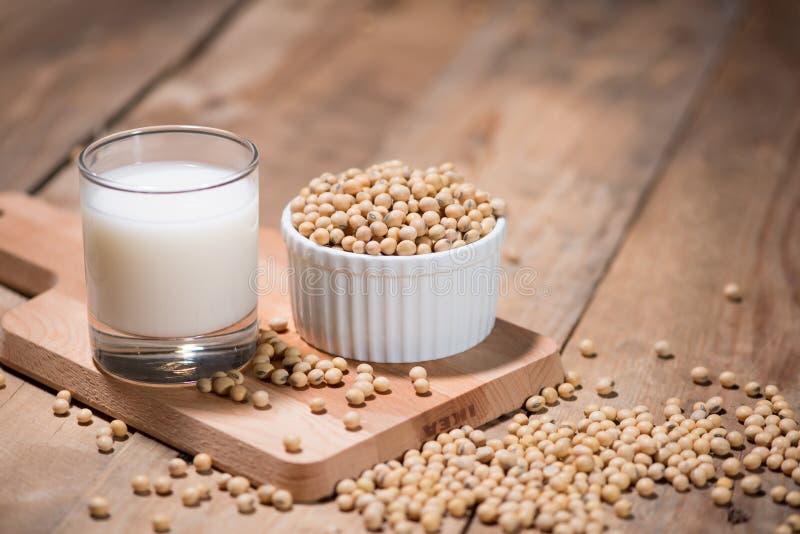 在匙子的豆奶或大豆牛奶和大豆豆在木桌上 免版税库存图片
