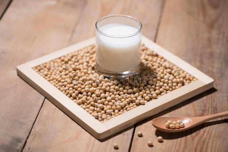 在匙子的豆奶或大豆牛奶和大豆豆在木桌上 免版税库存照片