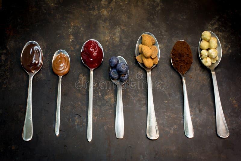 在匙子, CHOCLATE, RASBERRIES,可可粉,杏仁,草莓的自然食物酥皮点心成份 免版税库存图片