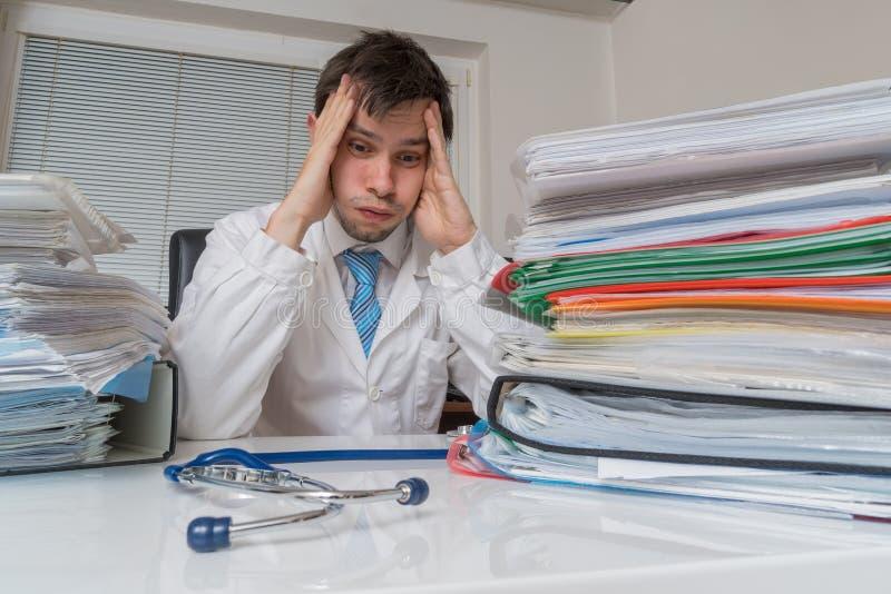在医学概念的官僚 疲乏的劳累过度的医生有在书桌上的许多文件 库存图片