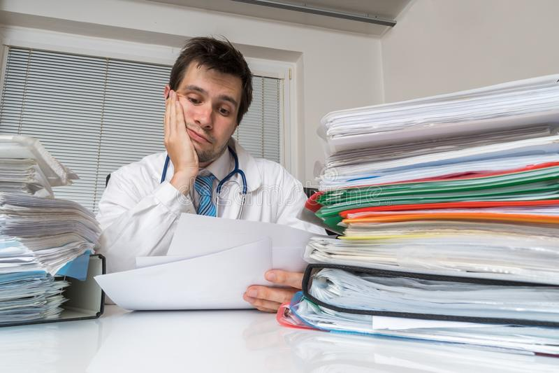 在医学概念的官僚 疲乏的劳累过度的医生读医疗报告 在书桌上的许多文件 免版税库存照片