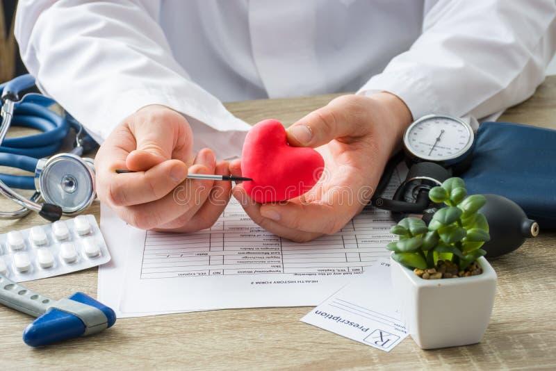 在医生任命医师在手边显示对卡片心脏耐心形状与焦点的与器官 场面解释的耐心caus 免版税图库摄影