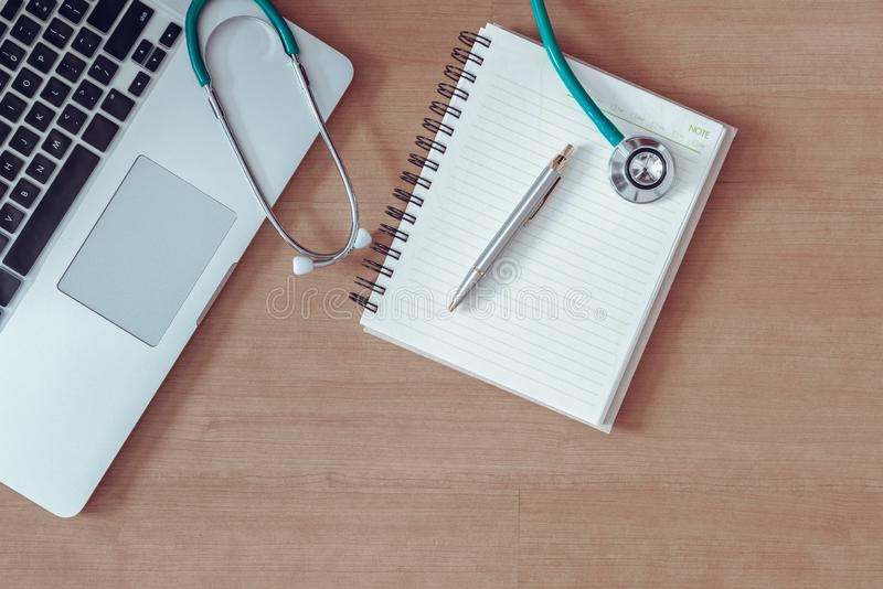 在医生办公室桌和设备工具,表审查的耐心健康工作区桌面的听诊器 科学和 免版税库存图片