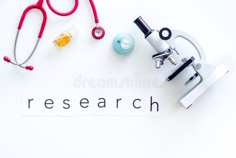 在医生工作书桌上的医学化验有显微镜、听诊器、试管和词研究白色背景顶视图的 免版税库存图片
