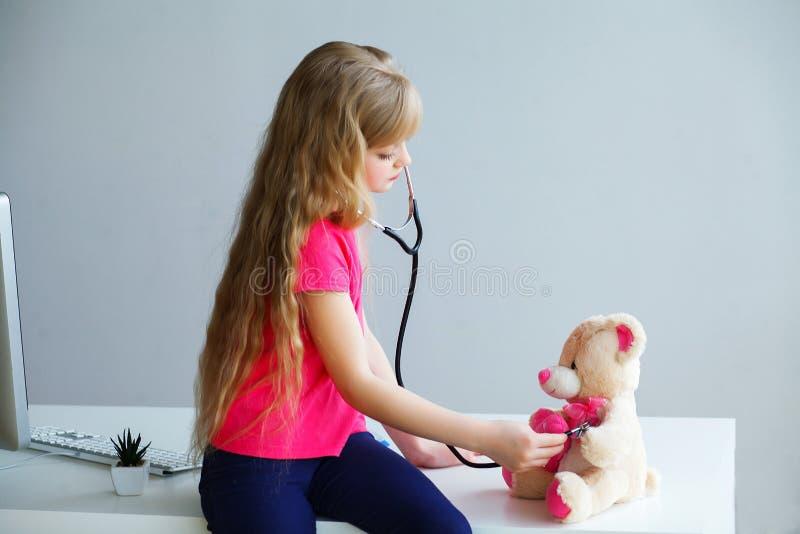 在医生玩具熊和听诊器的小女孩戏剧 图库摄影