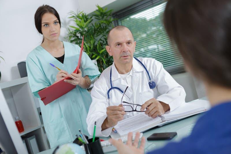 在医疗办公室篡改并且护理谈话与患者 图库摄影