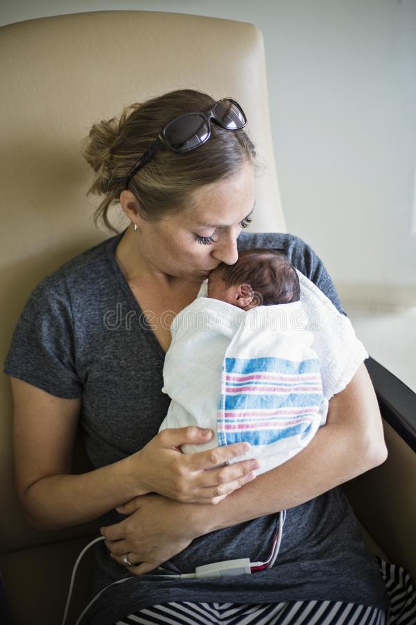 在医院照顾亲吻她新出生的早产儿 免版税库存照片