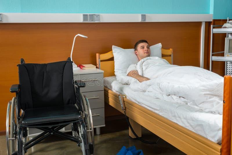 在医院病床上的年轻哀伤的男性不适的患者报道了机智 库存图片