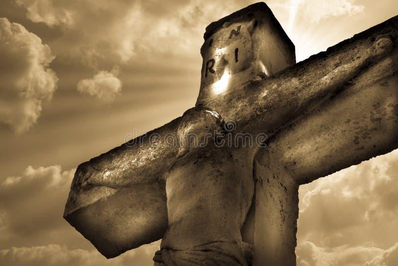 在十字架上钉死在天空背景的耶稣基督雕象 库存图片