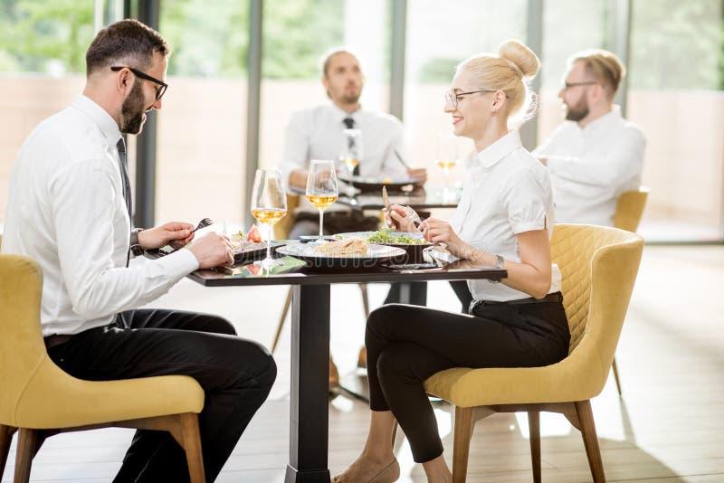 在午餐期间的商人在餐馆 免版税库存图片
