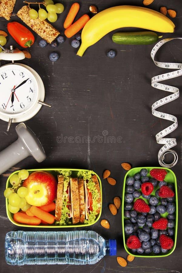 在午餐盒、测量的磁带和警报的健康&健身食物 免版税库存照片