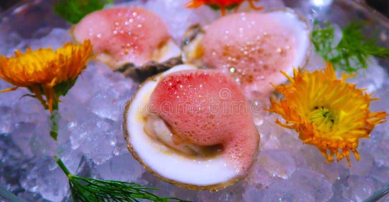 在半壳食家的牡蛎有在冰碗的花的 免版税库存照片