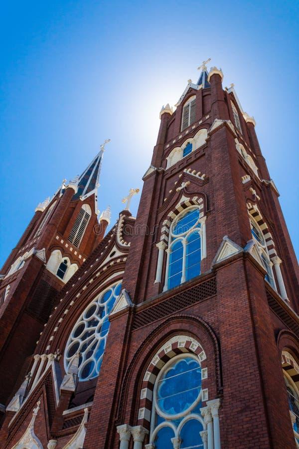 在华丽哥特式复兴教会外部的阳光背后照明 免版税库存图片