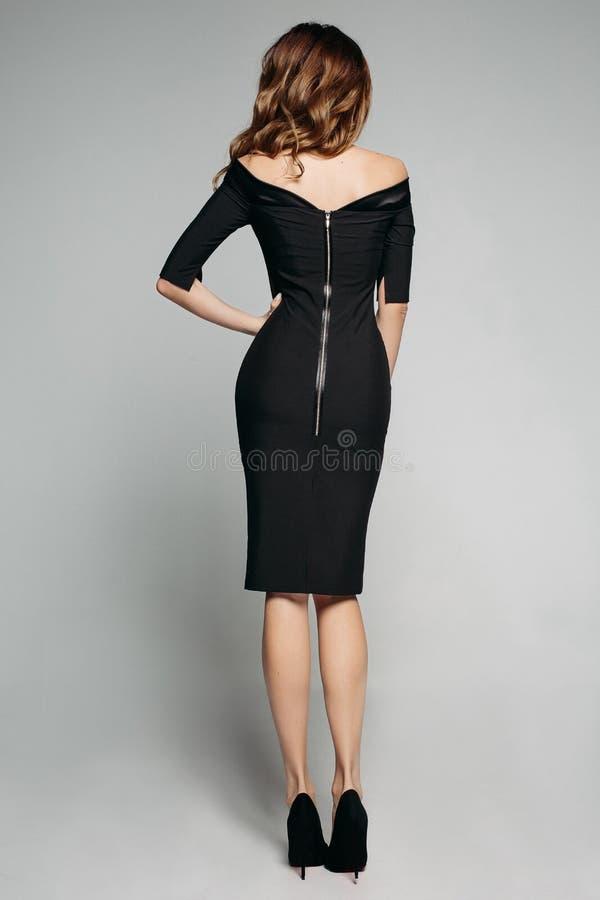 在华美的典雅的黑礼服和高hee的惊人亭亭玉立的模型 免版税库存照片