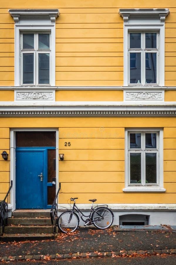 在卑尔根老镇骑自行车和一个老黄色房子 库存照片