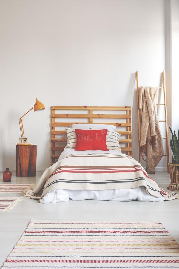 在单人床上的红色枕头与在宽敞卧室内部,与拷贝空间的真正的照片的镶边卧具在空的墙壁上 免版税库存照片