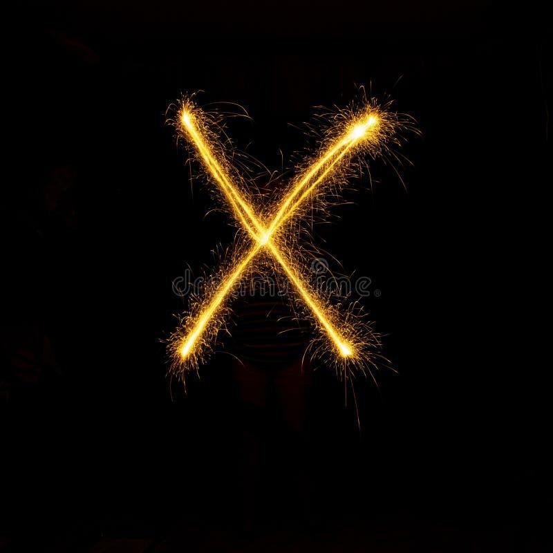 在单字母黑的背景的字母表闪烁发光物 库存照片