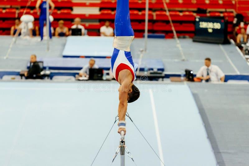 在单杠的体操运动员锻炼 免版税库存图片