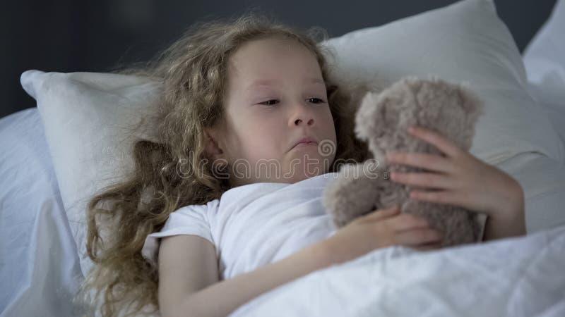 在单独床上的凄惨的女孩与眼睛有很多泪花,错过的妈咪 图库摄影