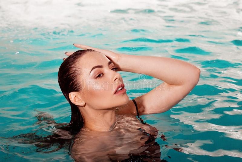 在单独水池的性感的年轻秀丽游泳 温泉和放松 库存图片