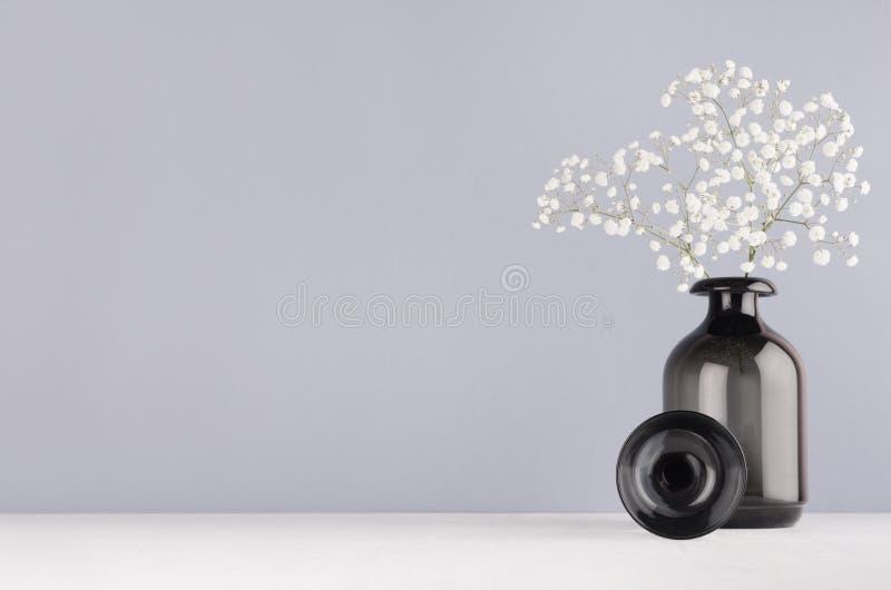在单色灰色颜色的简单的最低纲领派春天内部-小白花黑玻璃圈子和花瓶和花束  库存图片