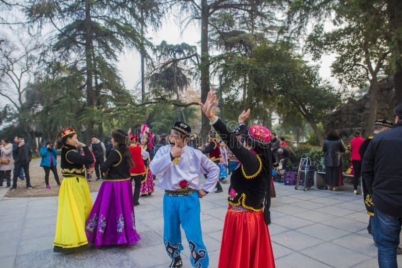 在南京xuanwu江苏省的湖公园,有喜欢新疆舞蹈愉快地经常跳舞的一群的人, 免版税库存照片
