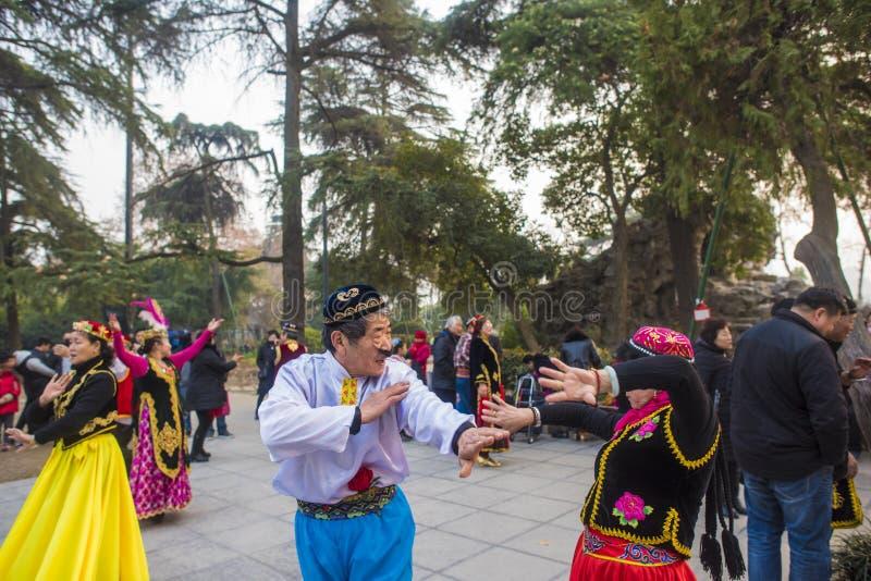 在南京xuanwu江苏省的湖公园,有喜欢新疆舞蹈愉快地经常跳舞的一群的人, 免版税库存图片