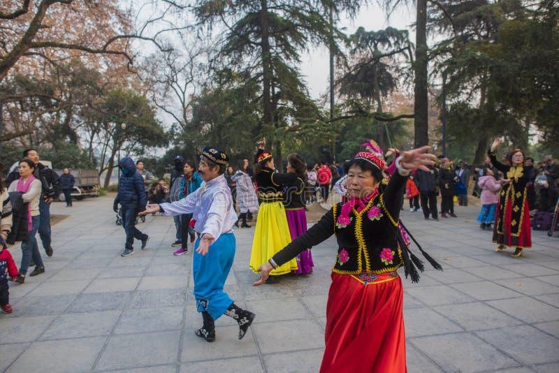 在南京xuanwu江苏省的湖公园,有喜欢新疆舞蹈愉快地经常跳舞的一群的人, 图库摄影